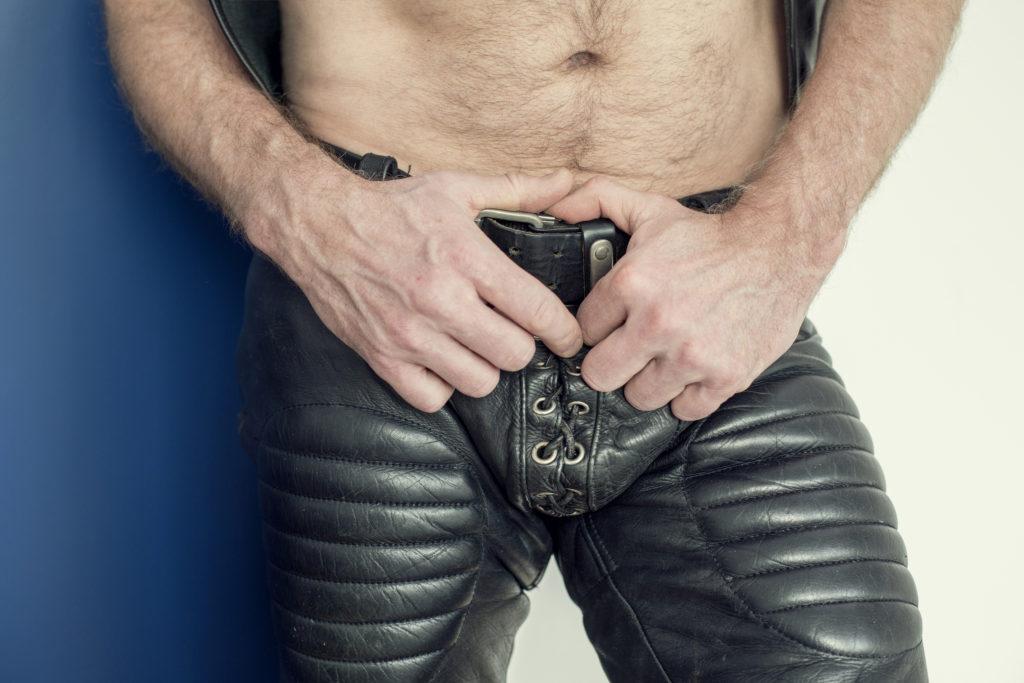 close-up of man wearing black fetish leather pants