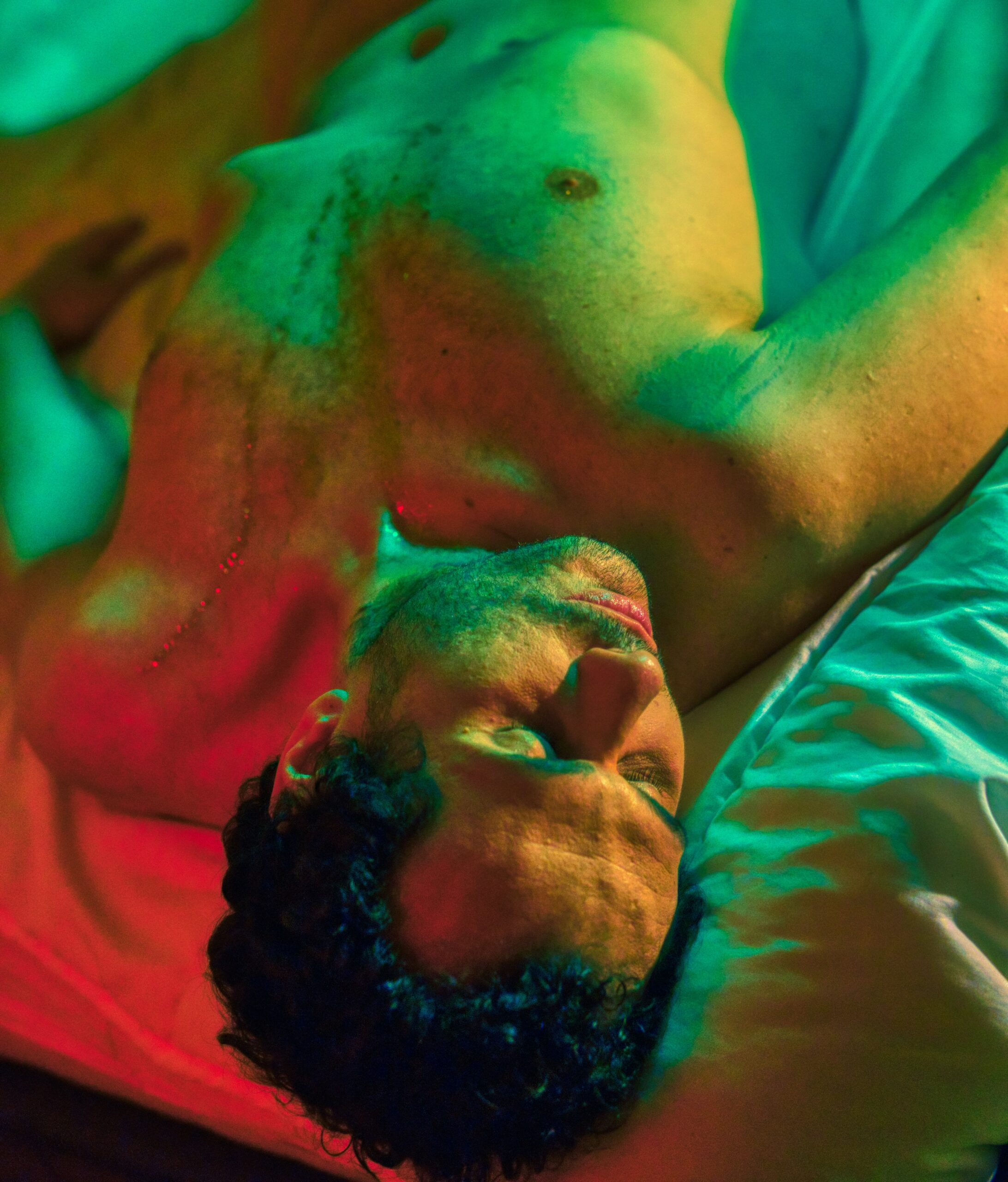 Topless man lying on bed - Sensual, erotic and intimate portrait of a naked guy